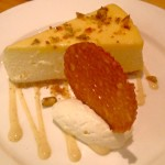 Mango cheesecake with passion fruit curd, pistachio praline, white chocolate & vanilla sauce, brandy snap biscuit